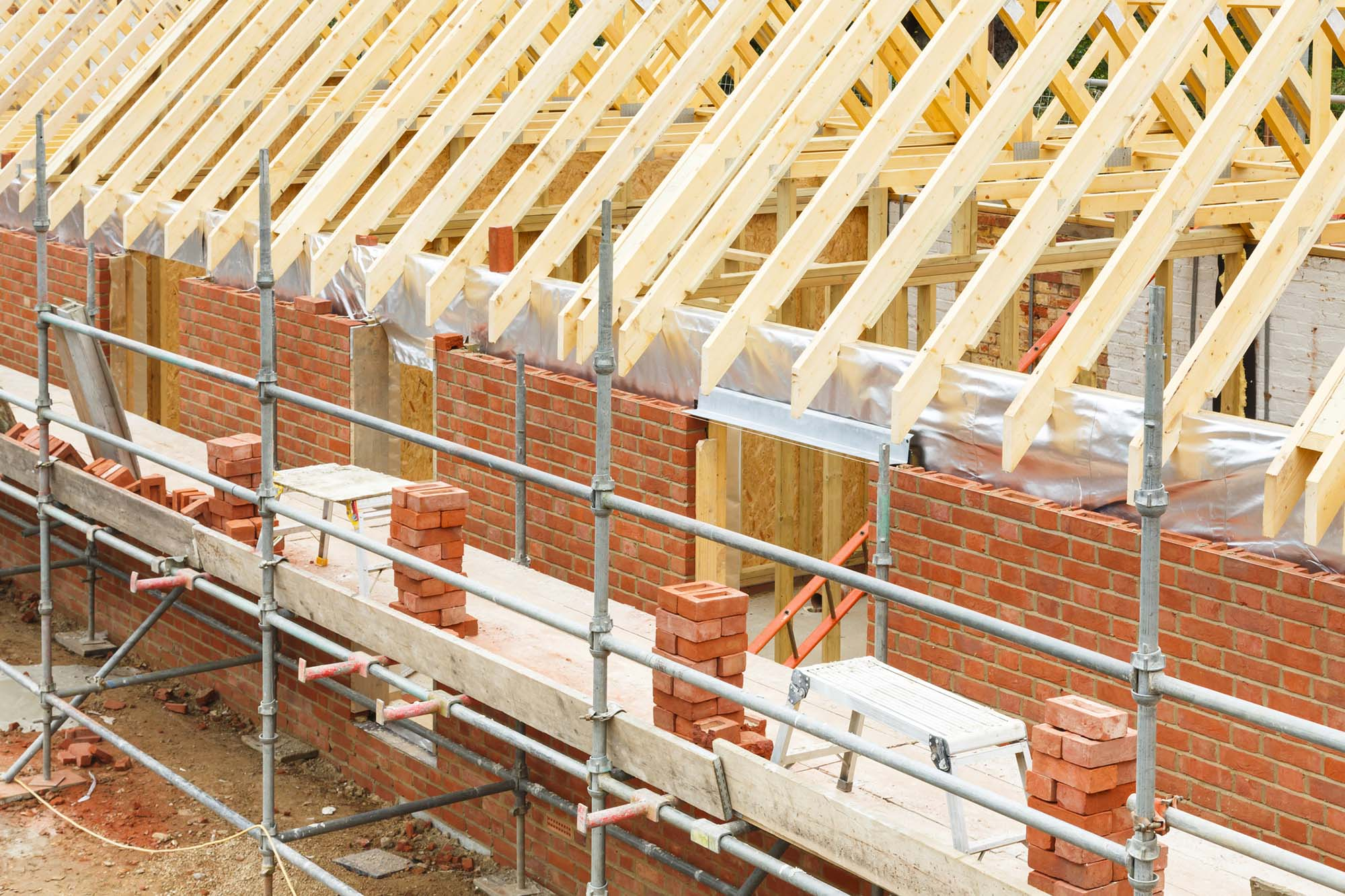 Houseing in the process of being built with brick and wood roofing